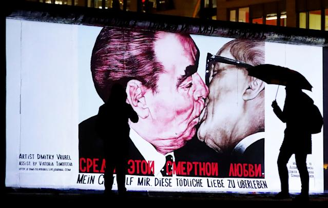People stand in front of a projection depicting former Soviet leader Leonid Brezhnev kissing his East German counterpart Erich Honecker, on the East Side Gallery, the largest remaining part of the former Berlin Wall, November 4, 2019. Credit: Reuters/Fabrizio Bensch