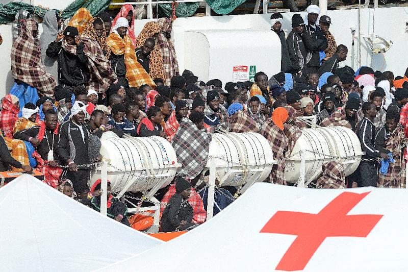 "Would be immigrants wait to disembark in the port of Catania, on the island of Sicily on March 21, 2017 from the ship ""Aquarius"" following a rescue operation in the Mediterranean sea, where some 946 would be immigrants have been rescued"