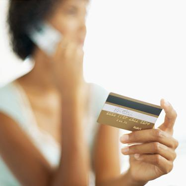 Close-up-of-a-young-woman-talking-on-phone-while-holding-credit-card_web