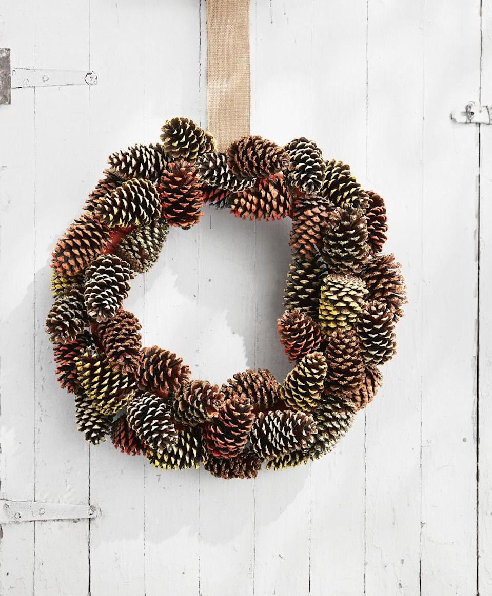 """<p><a href=""""https://www.countryliving.com/diy-crafts/how-to/g312/all-about-pinecones-1206/"""" rel=""""nofollow noopener"""" target=""""_blank"""" data-ylk=""""slk:Pine cones"""" class=""""link rapid-noclick-resp"""">Pine cones</a> are the most inexpensive crafting material out there, and make beautiful additions to <a href=""""https://www.countryliving.com/diy-crafts/g1988/fall-craft-projects/"""" rel=""""nofollow noopener"""" target=""""_blank"""" data-ylk=""""slk:fall wreaths"""" class=""""link rapid-noclick-resp"""">fall wreaths</a>. You can pick up a few right in your own backyard!</p><p><strong>Make the wreath:</strong> Wrap a 16-inch wreath form with burlap ribbon and loop a piece around the wreath form for hanging. Paint the tip of 40 pine cones in fall colors such as orange, yellow, and beige with acrylic paint. Brush the tips of 10 pine cones with matte Mod Podge and sprinkle with gold and copper glitter. once dry, wrap an 18-inch length of floral wire around the base of each pine cone and twist tie around the wreath form to secure, layering and overlapping them as you go.</p>"""