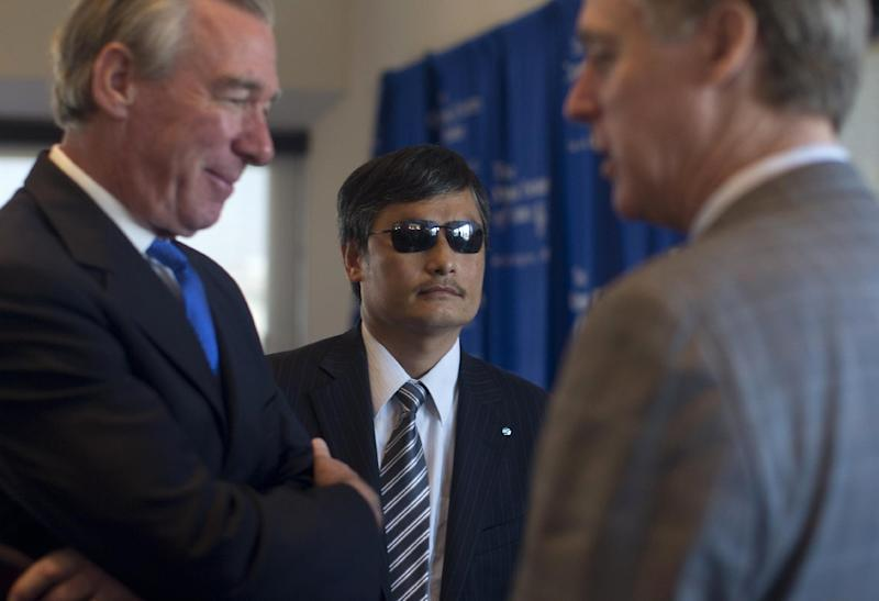 Chinese activist Chen Guangcheng, flanked by Catholic University of America President John Garvey, left, and Richard Swett, Treasurer of the Lantos Foundation for Human Rights and Justice waits to speak at the National Press Club in Washington, Wednesday, Oct. 2, 2013. Guangcheng says he has new affiliations with Lantos Foundation for Human RIghts and Justice, the Catholic University of America and the William E. and Carol G. Simon Center on Religion and Constitution of the Witherspoon Institute after leaving New York University under disputed circumstances. (AP Photo/Carolyn Kaster)