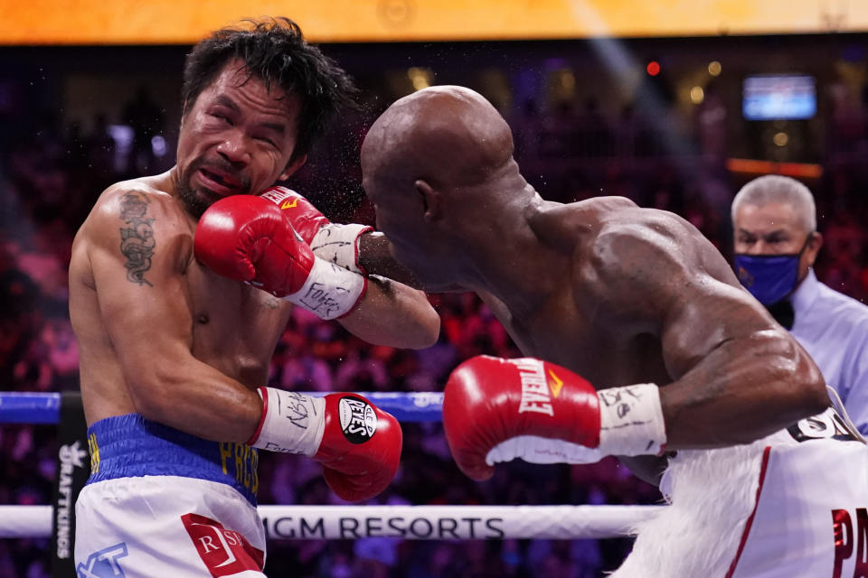 Manny Pacquiao, left, of the Philippines, is hit Yordenis Ugas, of Cuba, in a welterweight championship boxing match Saturday, Aug. 21, 2021, in Las Vegas. (AP Photo/John Locher)