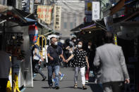 A couple wearing face masks walk through a path lined with restaurants during lunch time in Tokyo, Friday, Sept. 10, 2021. (AP Photo/Hiro Komae)