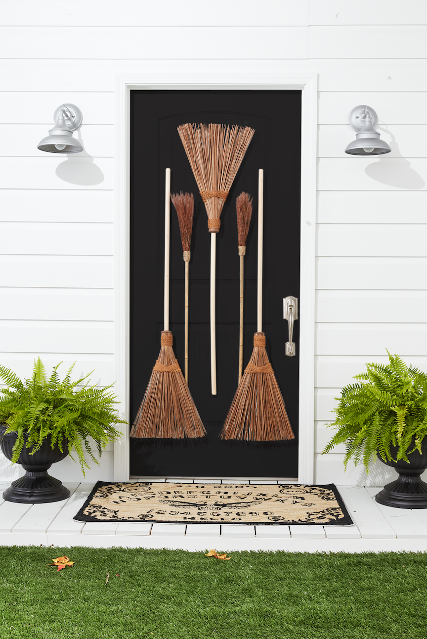 """<p>Pay homage to everyone's favorite Halloween character with this fun idea. All you need are a few vintage brooms and a witchy attitude to make it happen!</p><p><strong>Assemble the Brooms: </strong>Drill a small hole in the handle of two large outdoor brooms. Hammer five small nails in front door. Hang two brooms, right sides up, through holes. Hang a third large broom and two small """"witches' brooms"""" by threading the bristles over the remaining three nails. </p>"""