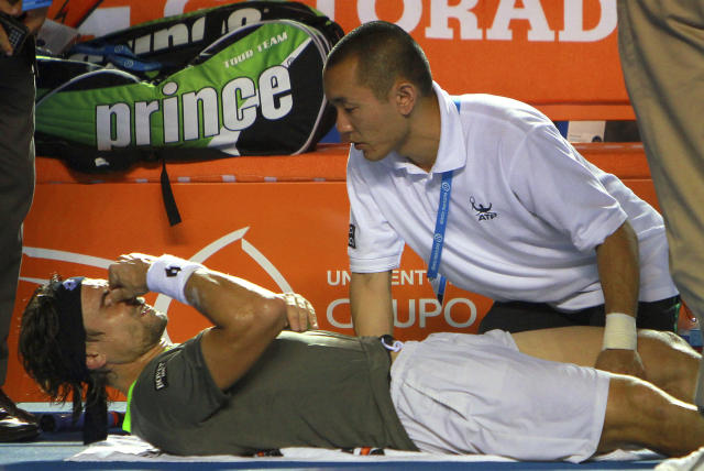 Spain's David Ferrer is treated after injuring his right leg while playing South Africa's Kevin Anderson at the Mexican Tennis Open in Acapulco, Mexico, Thursday, Feb. 27, 2014. Ferrer retired from the match and Anderson won the match. (AP Photo/Hugo Avila, JAM MEDIA)