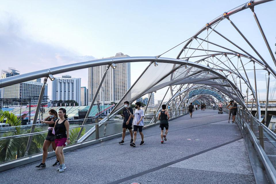 People wearing face masks as a precaution against the spread of covid-19 walk along the Helix Bridge at Marina Bay, Singapore.