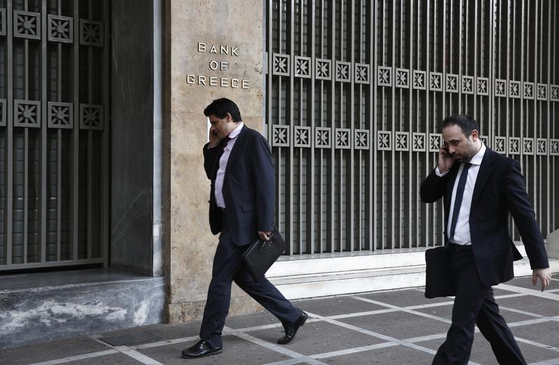 Two men speak on their phones as they walk outside the Bank of Greece in Athens