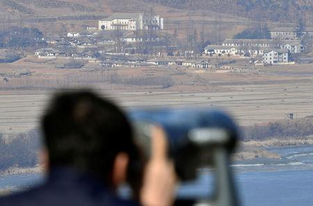 A man looks towards North Korea's propaganda village Kaepoong through a pair of binoculars from an observation platform, near the demilitarized zone separating the two Koreas in Paju, South Korea, February 12, 2017. Shin Woong-su/News1 via REUTERS