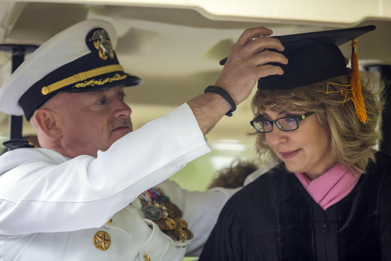 Former U.S. Rep. Gabrielle Giffords leans forward as her husband, Mark Kelly, retired space shuttle commander, adjusts her mortarboard as they ride in the procession for the 153rd Commencement at Bard College, Saturday, May 25, 2013, in Annandale-on-Hudson, N.Y. They delivered the commencement address, and Giffords received an honorary degree. (AP Photo/Philip Kamrass)