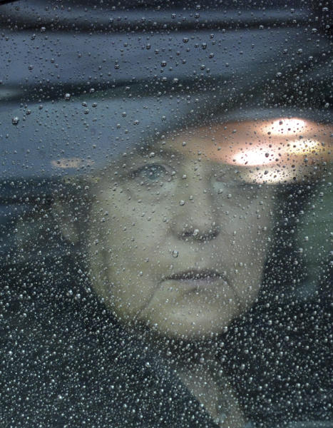 German Chancellor Angela Merkel looks out from behind raindrops on her car window as she arrives for an EU summit in Brussels on Friday, Nov. 23, 2012. The prospect of failure hangs over a European Union leaders' summit intended to lay out the 27-country bloc's long-term spending plans. While heavyweights like Britain and France are pulling in opposite directions, smaller members are threatening to veto a deal to make themselves heard. (AP Photo/Geert Vanden Wijngaert)