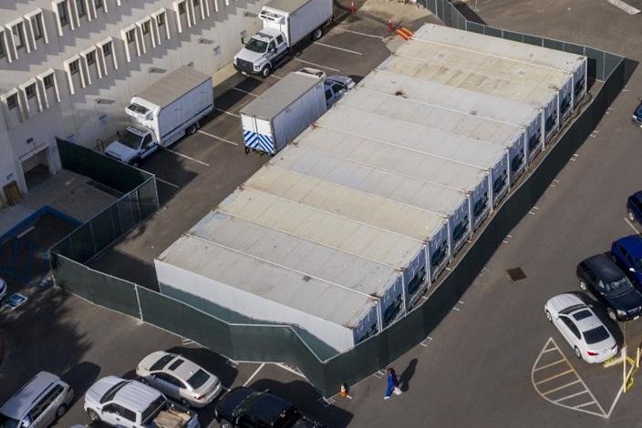 LOS ANGELES, CA - JANUARY 07: A dozen refrigerated storage containers hum in the parking lot at the Los Angeles County Coroner complex on Thursday, Jan. 7, 2021 in Los Angeles, CA. (Brian van der Brug / Los Angeles Times)