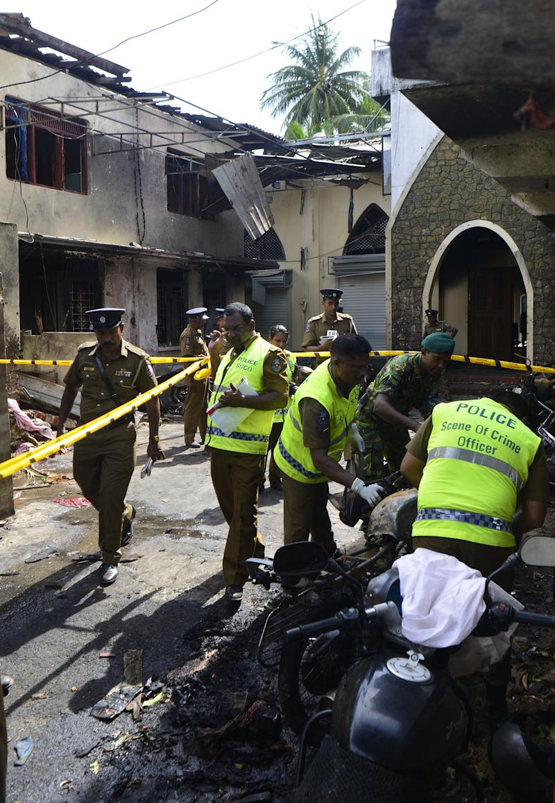Sri Lankan security personnel and police investigators look through debris outside Zion Church on April 21, 2019 following an explosion in Batticaloa, Sri Lanka.