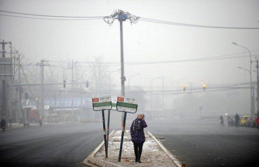 A woman waits for a bus in the haze in Beijing in December 2011. Beijing's government on Friday bowed to a vocal online campaign for a change in the way air quality is measured in the Chinese capital, one of the world's most polluted cities