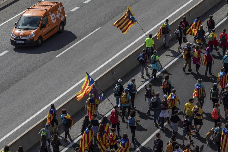 Catalan pro-independence demonstrators march near Navas, Spain, Wednesday, Oct. 16, 2019. Thousands of people have joined five large protest marches across Catalonia that are set to converge on Barcelona, as the restive region reels from two straight days of violent clashes between police and protesters. The marches set off from several Catalan towns and aimed to reach the Catalan capital by Friday. (AP Photo/Bernat Armangue)