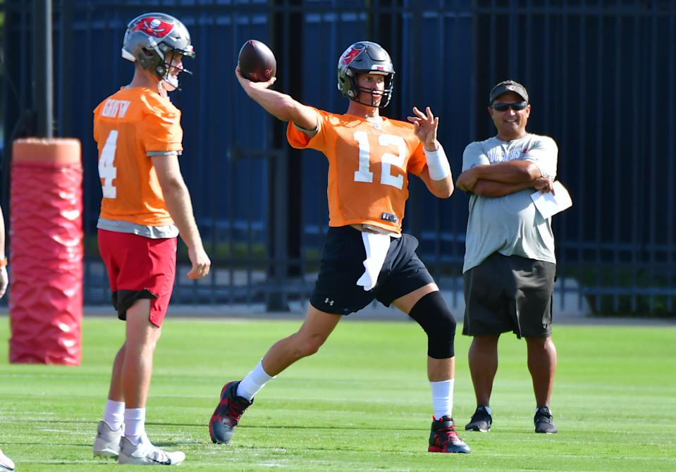 Ryan Griffin #4 (L) and quarterback coach Clyde Christensen (R) look on as Tom Brady #12 of the Tampa Bay Buccaneers throws a pass during the Buccaneers Mini-Camp at AdventHealth Training Center on June 08, 2021 in Tampa, Florida. (Photo by Julio Aguilar/Getty Images)