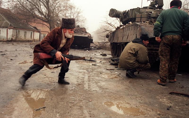 Russian troops and a local volunteer take cover during fighting in Chechnya in 1995 - Credit: OLEG NIKISHIN/AFP