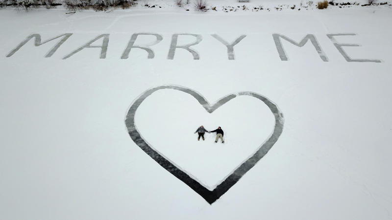 In this Jan. 7, 2018 photo provided by Ed Becker, Gavin Becker and his long-time girlfriend Olivia Toft lay in the snow after he proposed on Eight Crow Wing Lake near Nevis, Minn. Becker had his family's help etching out the big question with a snow blower in 25-foot-tall letters and a huge heart in the snow on the frozen lake. Then Gavin rented a plane and took Toft, who said yes, for a ride over the lake to see where his father took photos of the event. (Ed Becker via AP)