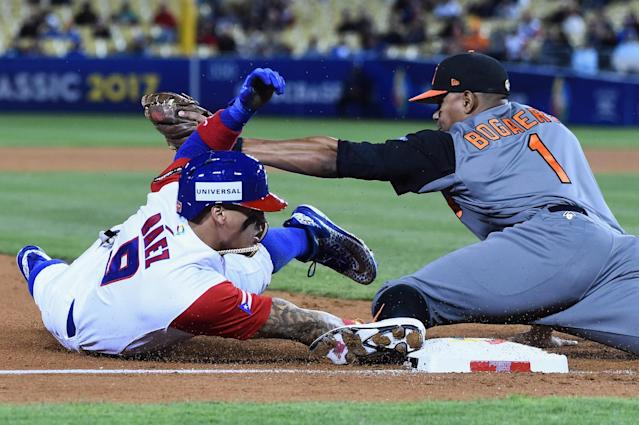 Javy Baez evades a tag from Xander Bogaerts. (Getty Images)