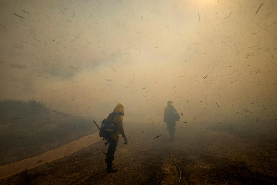 Firefighters face strong winds as they head up a hillside to battle a wind driven wildfire near Irvine, California.