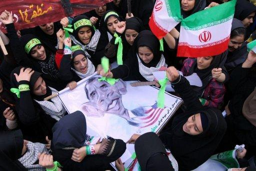 "Iranian women hold a banner bearing a cartoon of US President Barack Obama, outside the former US embassy in Tehran. Thousands of Iranians chanting ""Death to America"" rallied to mark the 33rd anniversary of the seizure of the US embassy in Tehran"