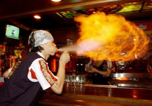 A South Korean bartender creates a ball of flame by blowing alcohol from his mouth