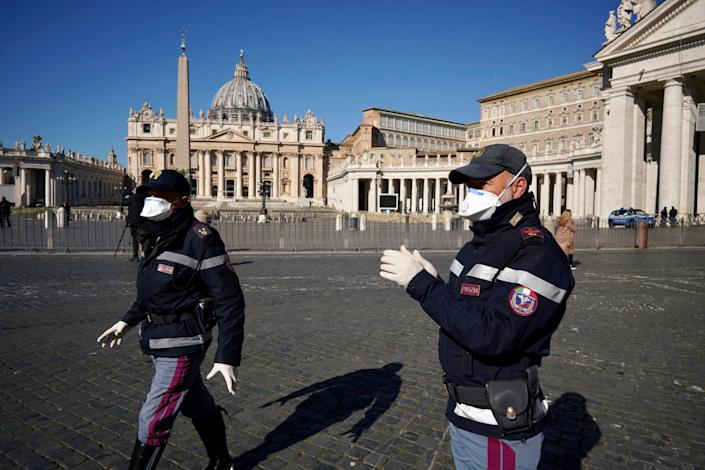 Police officers wearing masks patrol an empty St. Peter's Square at the Vatican, Wednesday, March 11, 2020. Pope Francis held his weekly general audience in the privacy of his library as the Vatican implemented Italy's drastic coronavirus lockdown measures, barring the general public from St. Peter's Square and taking precautions to limit the spread of infections in the tiny city state.For most people, the new coronavirus causes only mild or moderate symptoms, such as fever and cough. For some, especially older adults and people with existing health problems, it can cause more severe illness, including pneumonia. (AP Photo/Andrew Medichini)