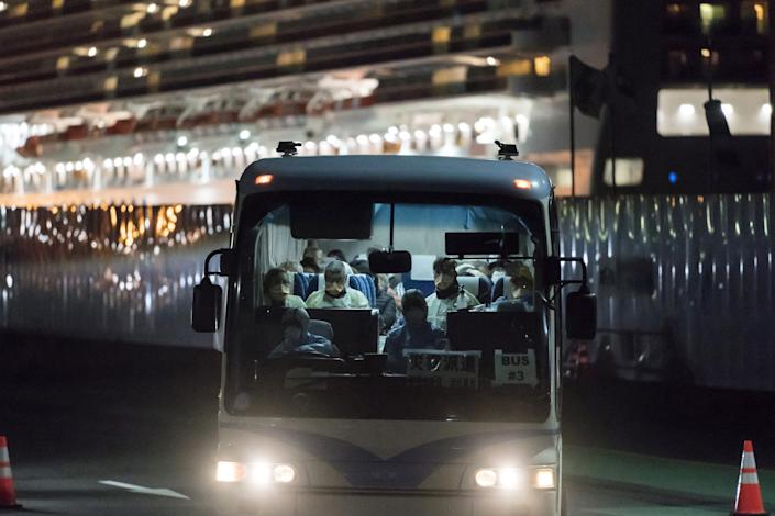 A bus carrying passengers, who will board the Qantas aircraft chartered by the Australian government, from the quarantined Diamond Princess cruise ship drive at the Daikoku Pier on February 19, 2020 in Yokohama, Japan.