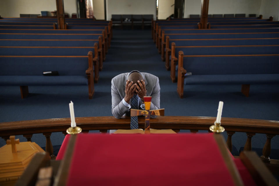 In this May 28, 2021, photo, Rev. Robert R.A. Turner, pastor of the historic Vernon African Methodist Episcopal Church, prays in the sanctuary of the church between meetings around centennial commemorations of the Tulsa Race Massacre in Tulsa, Okla. Only the basement remained of the church, partially destroyed in the massacre in 1921 that destroyed the area known as Black Wall Street. (AP Photo/John Locher)