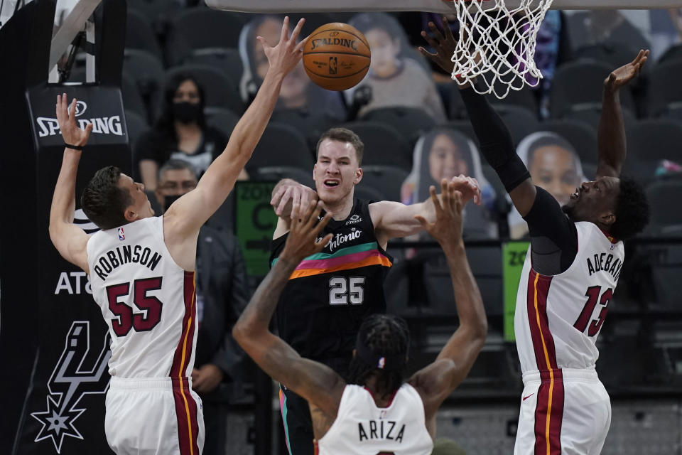 San Antonio Spurs center Jakob Poeltl (25) passes the ball as he is pressured by Miami Heat defenders Duncan Robinson (55), Trevor Ariza (8) and Bam Adebayo (13) during the second half of an NBA basketball game in San Antonio, Wednesday, April 21, 2021. (AP Photo/Eric Gay)