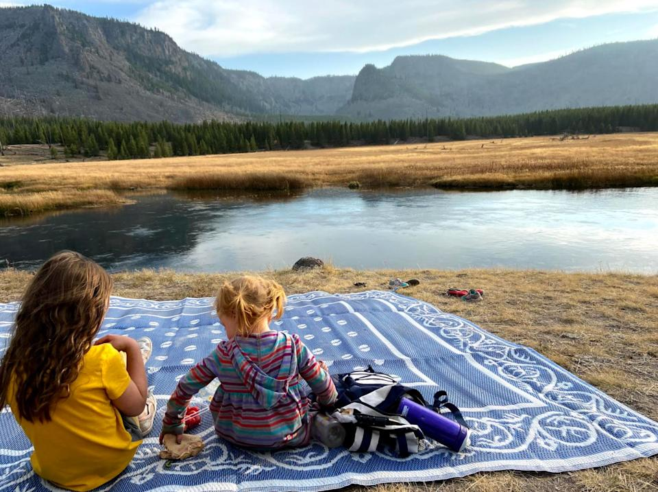 The author's daughters enjoying a picnic along the Firehole River in Yellowstone National Park in October 2020. (Photo: Courtesy of Kelly Burch)