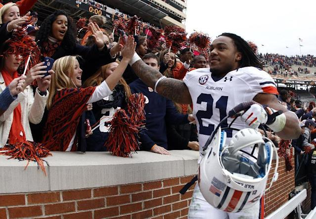 Auburn running back Tre Mason (21) celebrates with fans after an NCAA college football game against Tennessee on Saturday, Nov. 9, 2013, in Knoxville, Tenn. Auburn won 55-23. (AP Photo/Wade Payne)