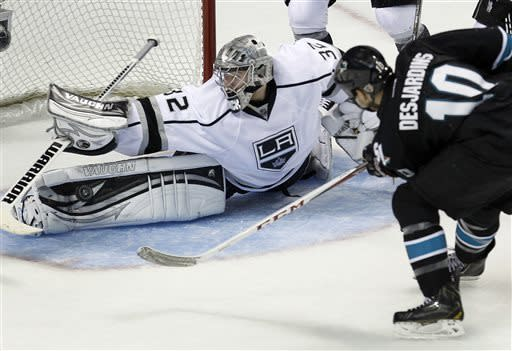 Los Angeles Kings goalie Jonathan Quick (32) blocks a goal attempt against San Jose Sharks center Andrew Desjardins (10) during the second period in Game 3 of their second-round NHL hockey Stanley Cup playoff series, Saturday, May 18, 2013, in San Jose, Calif. (AP Photo/Tony Avelar)