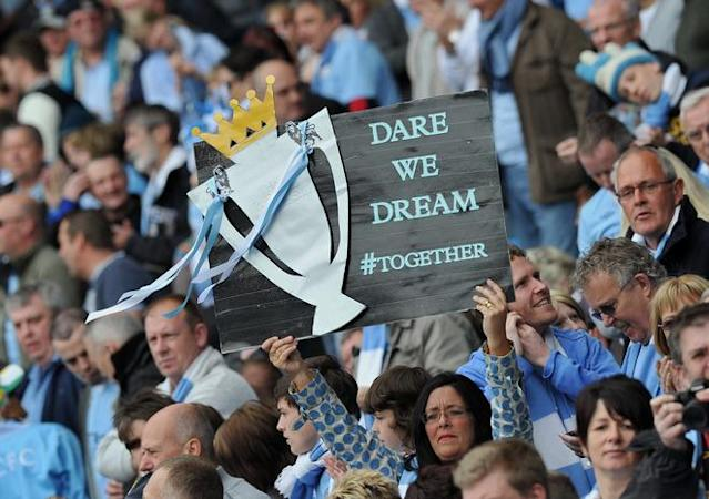 "Manchester City supporters hold a home-made trophy banner aloft before the English Premier League football match between Manchester City and Queens Park Rangers at The Etihad stadium in Manchester, north-west England on May 13, 2012. AFP PHOTO/PAUL ELLIS RESTRICTED TO EDITORIAL USE. No use with unauthorized audio, video, data, fixture lists, club/league logos or ""live"" services. Online in-match use limited to 45 images, no video emulation. No use in betting, games or single club/league/player publications.PAUL ELLIS/AFP/GettyImages"