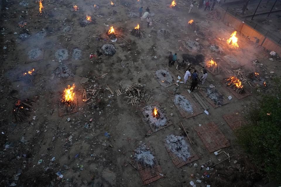 A view of a crematorium ground showing funeral pyres during a mass cremation of victims, who died due to the coronavirus disease (COVID-19), at a crematorium in New Delhi on April 22, 2021. India reported over 3.14 lakh new Covid-19 cases on Thursday, the highest-ever daily count recorded anywhere. 2,104 have succumbed to the disease in the last 24 hours, as per the Union health ministry.  (Photo by Mayank Makhija/NurPhoto via Getty Images)