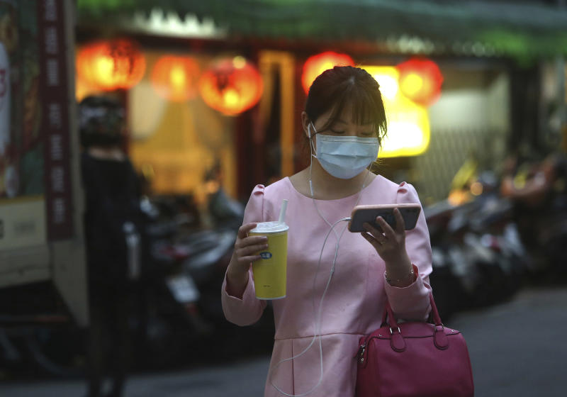 A woman her protective face mask balances her large-sized cup while watching her smart phone in Taipei, Taiwan, Tuesday, March 31, 2020. The new coronavirus causes mild or moderate symptoms for most people, but for some, especially older adults and people with existing health problems, it can cause more severe illness or death. (AP Photo/Chiang Ying-ying)