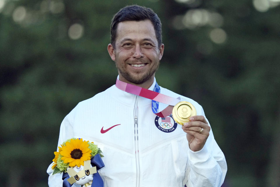 FILE - In this Aug. 1, 2021, file photo, Xander Schauffele, of the United States, holds his gold medal in the men's golf at the 2020 Summer Olympics in Kawagoe, Japan. The 2020 US Ryder Cup team has six rookies, including gold medalist Xander Schauffele. (AP Photo/Andy Wong, File)
