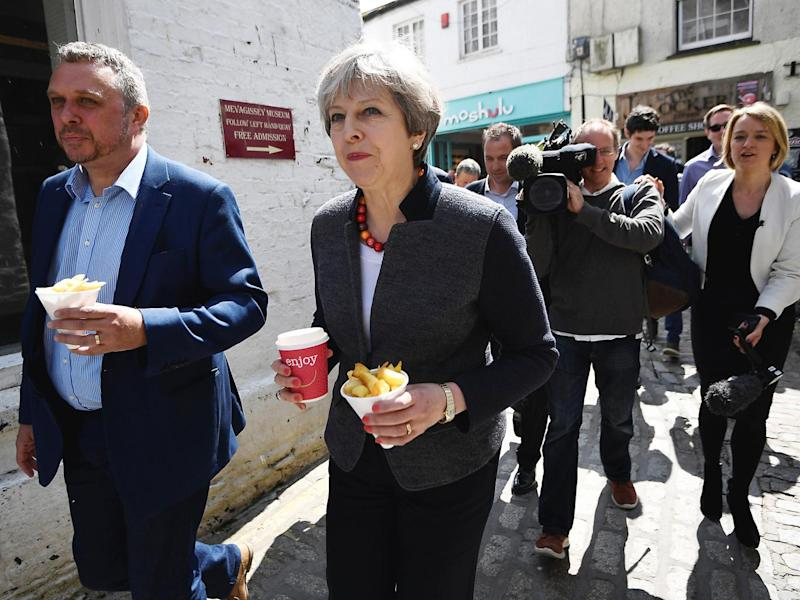Britain's Prime Minister Theresa May is followed by journalists as she carries some chips during a campaign stop in Mevagissey, Cornwall (Reuters)