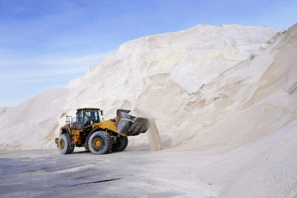 A front loader works at a large pile of road salt, Wednesday, Dec. 16, 2020, in Chelsea, Mass., as preparation continues for a storm that is expected to dump a foot or more of snow throughout the Northeast. (AP Photo/Elise Amendola)