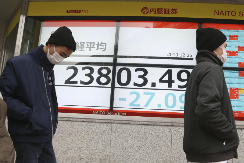 People walk by an electronic stock board of a securities firm in Tokyo, Wednesday, Dec. 25, 2019. Chinese and Japanese stocks declined Wednesday while most other Asian markets were closed for Christmas Day. (AP Photo/Koji Sasahara)