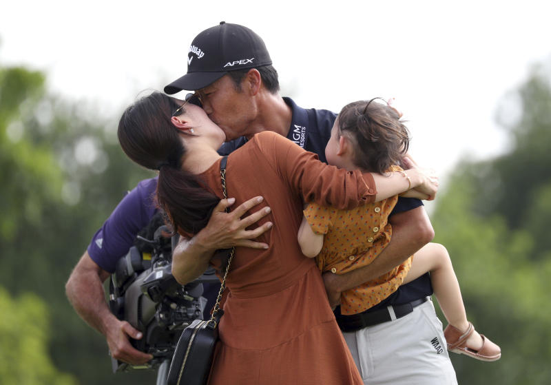 Kevin Na, center, kisses his wife Jullianne as he holds daughter Sophia after winning the Charles Schwab Challenge golf tournament Sunday, May 26, 2019, in Fort Worth, Texas. (AP Photo/ Richard W. Rodriguez)