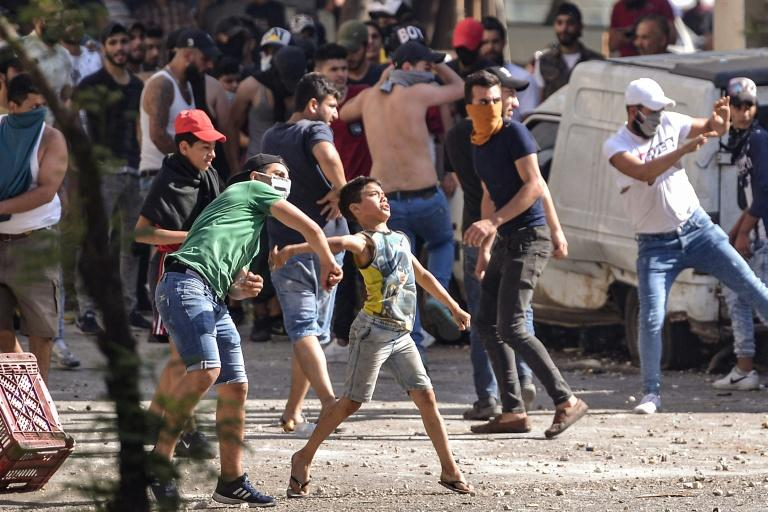 Lebanese anti-government protesters hurl rocks at soldiers amid clashes in the northern port city of Tripoli, on the third consecutive day of angry demonstrations across the country (AFP Photo/Fathi AL-MASRI)