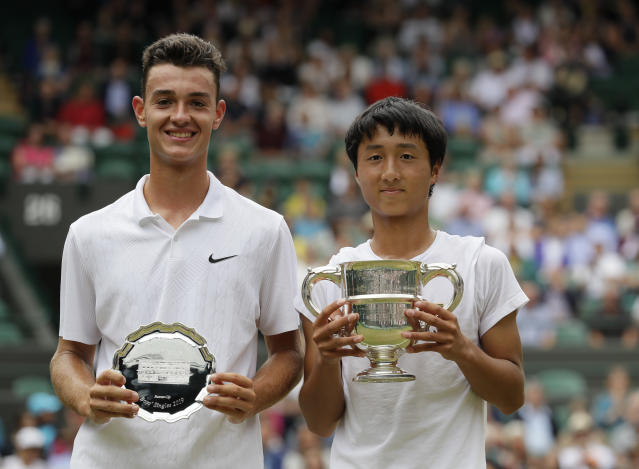 Japan's Shintaro Mochizuki and Spain's Carlos Gimeno Valero pose with the trophies after the boys' singles final match of the Wimbledon Tennis Championships in London, Sunday, July 14, 2019. (AP Photo/Kirsty Wigglesworth)