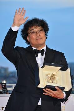 A man in a tuxedo waves and carries an award.