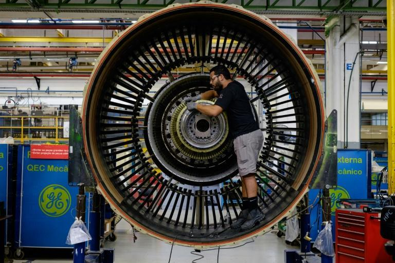 A man works with a jet engine at General Electric (GE) Celma, GE's aviation engine overhaul facility in Rio de Janeiro, Brazil (AFP Photo/YASUYOSHI CHIBA)