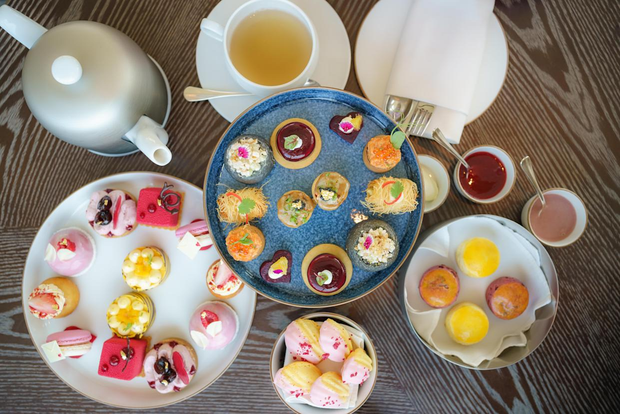 Top view of afternoon tea, cakes and snacks with a teapot in the background.