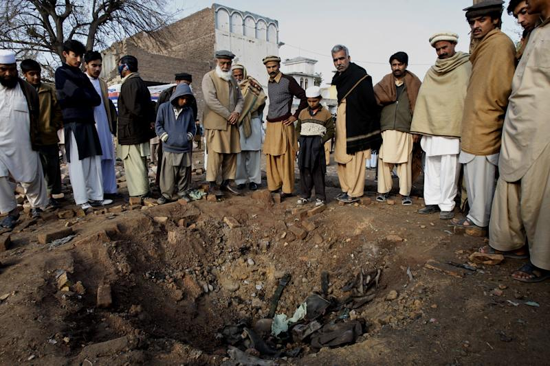 Local residents examine a crater caused by Saturday night's car bombing by Taliban militants close to the international airport in Peshawar, Pakistan, Sunday, Dec. 16, 2012. Pakistani security forces cornered the last members of a group of Taliban militants who staged a deadly raid on an airport in the country's troubled northwest, and all five died in the ensuing Sunday firefight, officials said. (AP Photo/Mohammad Sajjad)