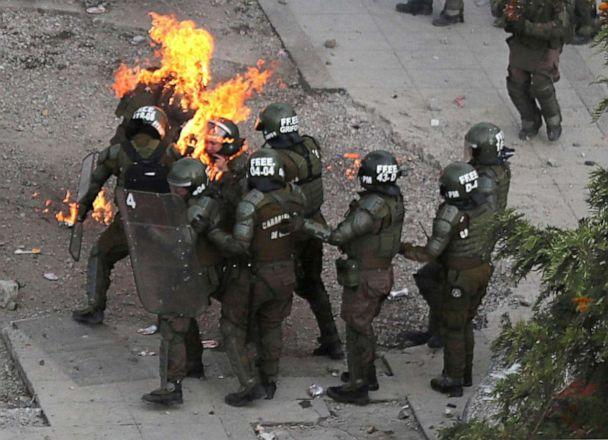 PHOTO: Riot police officers who are on fire are assisted by fellow officers during a protest against Chile's government in Santiago, Chile, Nov. 4, 2019. (Ivan Alvarado/Reuters)