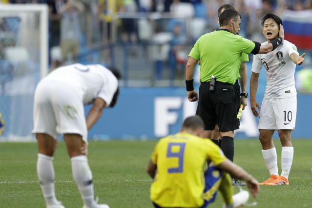 South Korea'sLeeSeung-woo, speaks with referee Joel Aguilar from El Salvador tend of the group F match between Sweden and South Korea at the 2018 soccer World Cup in the Nizhny Novgorod stadium in Nizhny Novgorod, Russia, Monday, June 18, 2018. the review resulted in a penalty for Sweden from which they scored the opening goal. (AP Photo/Petr David Josek)