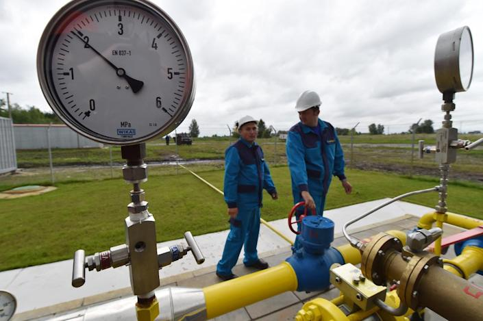 Employees look at a pipeline at the new East Poltava gas booster compressor station not far from Ukrainian city of Poltava on June 27, 2014 (AFP Photo/Sergei Supinsky)