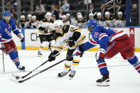 Boston Bruins' Fabian Lysell (68) looks to pass around New York Rangers' K'Andre Miller (79) during the third period of a preseason NHL hockey game, Tuesday, Sept. 28, 2021, at Madison Square Garden in New York. (AP Photo/Corey Sipkin).